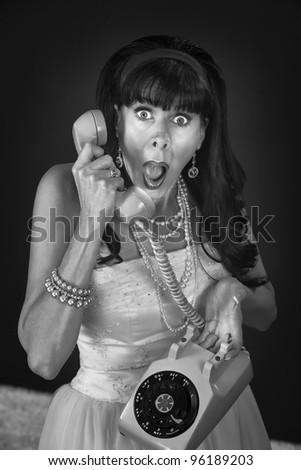 Shocked retro-styled woman holding telephone over maroon background