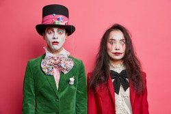 Shocked scary couple celebrate halloween have professional makeup and wear costumes pose next to each other against pink background. Man hatter with white face stands near spooky woman vampire