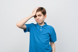 Shocked Serious boy 12-14 years old in casual blue t shirt, look puzzled and amazed, holding hand on head, staring at problem, forgot remember something, standing against light gray background, isolat