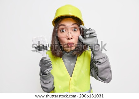 Shocked skilled Asian female designer holds painting brush redecorates house wears safety glasses hardhat and uniform isolated over white background. Stunned decorator with tool ready to work Foto stock ©