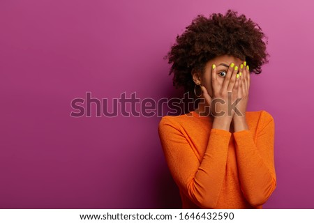 Shocked stunned Afro American woman hides face with both palms, stares through fingers, tells when horror over, has insecure frightened expression, waits for terrifying moment, watches scarying movie