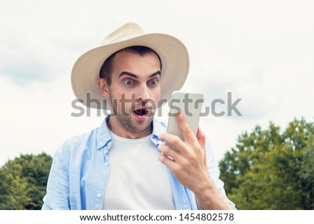 Shocked stunned cowboy with smartphone, attractive man amazed by good news, portrait, close up, toned