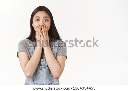 Shocked stunned gasping brunette asian girl open mouth cover lips hands look camera amazed cannot believe witnessed shook concerning accident stand white background speechless