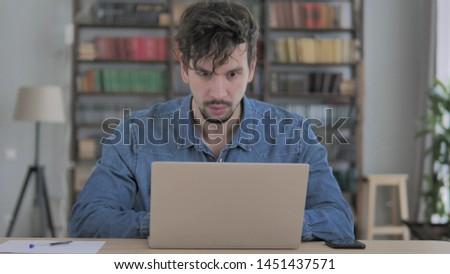 Shocked, Stunned Man Wondering and Working on Laptop