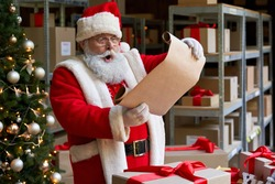 Shocked surprised old funny Santa Claus wearing costume holding parchment roll reading letter wish list preparing Christmas shipping delivery gifts presents parcels standing in workshop on xmas eve.