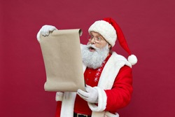 Shocked surprised old funny Santa Claus wearing costume holding parchment roll reading letter wish list preparing for Christmas holiday standing isolated on red background. Xmas wishlist concept.