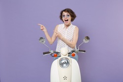 Shocked surprised young brunette woman in white dotted shirt glasses point index fingers aside on mock up copy space sitting driving moped isolated on pastel violet colour background studio portrait