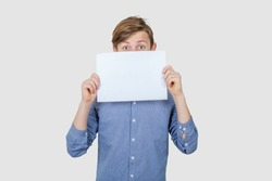Shocked Teenage boy covering his face with a empty white paper over white background. Teenage boy holding blank sheet of paper infront of his face.