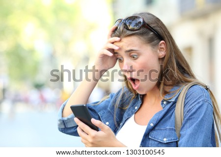 Shocked teenage girl checking smart phone discovering mistake content in the street #1303100545
