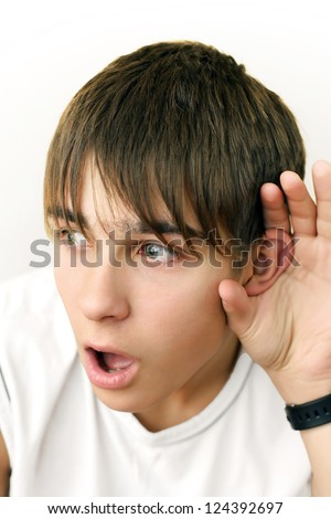 Shocked Teenager listen to something and keep his palm behind an ear