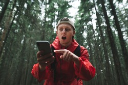 Shocked tourist man is pointing his finger on a smartphone, catching a signal, using the maps in the mountain forest. Surprised male hiker in a red raincoat is using his phone in the woods.