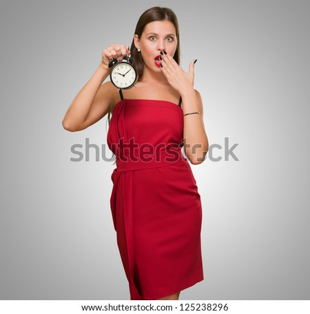 Shocked Woman Holding Alarm Clock against a grey background
