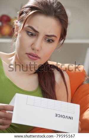 shocked woman holding bill or invoice at home