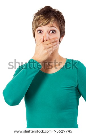 Shocked woman in green sweatshirt covering her mouth. Studio shot against a white background.
