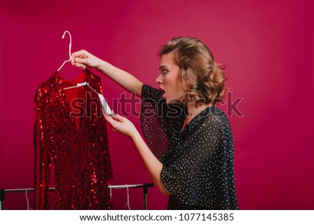 Shocked woman looking at price on sparkle red dress in boutique. Indoor portrait of amazed young female model holding hanger with expensive attire. #1077145385