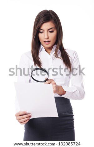 Shocked woman looking through a magnifying glass on documents