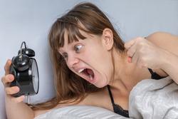 Shocked woman with alarm clock comes late to work because she oversleep - oversleeping concept