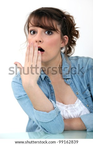 Shocked woman with her hand to her mouth