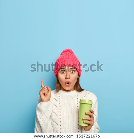 Shocked wondered woman points up with index finger, carries takeaway coffee, scared by something, keeps eyes bugged, wears rosy hat and white winter sweater, cannot believe in shocking relevation