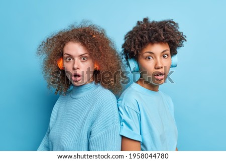 Shocked worried culy haired female best friends stare speechless have startled face expressions stand back to each other wear stereo headphones on ears dressed casually isolated over blue wall Stockfoto ©