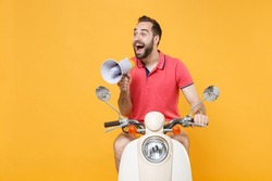 Shocked young bearded man guy in casual summer clothes driving moped isolated on yellow wall background studio portrait. Driving motorbike transportation concept. Scream in megaphone, looking aside
