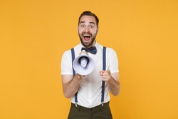 Shocked young bearded man 20s wearing white shirt bow-tie suspender posing standing screaming in megaphone pointing index finger on camera isolated on bright yellow color background studio portrait
