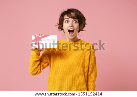 Shocked young brunette woman girl in yellow sweater posing isolated on pastel pink background studio portrait. People sincere emotions lifestyle concept. Mock up copy space. Holding gift certificate