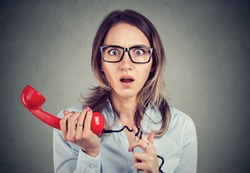 Shocked young business woman receiving bad news over the telephone