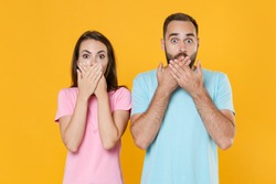Shocked young couple friends guy girl in blue pink t-shirts posing isolated on yellow wall background studio portrait. People emotions lifestyle concept. Mock up copy space. Covering mouth with hands.