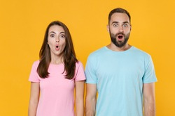 Shocked young couple two friends guy girl in blue pink t-shirts posing isolated on yellow background studio portrait. People sincere emotions lifestyle concept. Mock up copy space. Keeping mouth open.