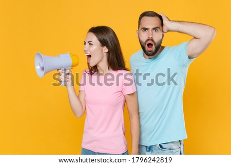 Shocked young couple two friends guy girl in blue pink t-shirts posing isolated on yellow wall background studio. People lifestyle concept. Mock up copy space. Screaming in megaphone put hand on head.