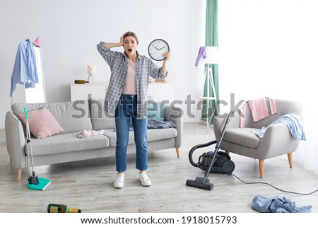 Shocked young lady with clock grabbing her head in terror, standing in messy room after party, too late to clean apartment before return of her parents. Space for text