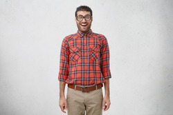 Shocked young male nerd wears old fashionable glasses, checkered shirt and trousers stares at camera, has funny look, poses against white studio background. Intelligent man with surprised expression