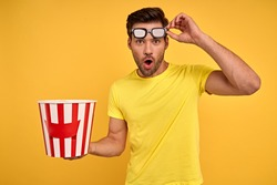 Shocked young man in casual clothes 3d glasses posing isolated on yellow wall background studio. People sincere emotions in cinema, lifestyle concept. Watching movie film, holding bucket of popcorn.
