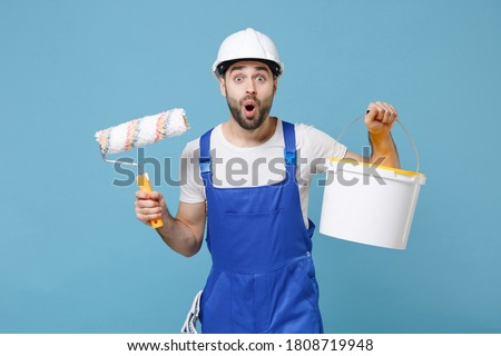 Shocked young man in coveralls protective helmet hardhat hold paint roller, bucket isolated on pastel blue wall background. Instruments accessories for renovation apartment room. Repair home concept