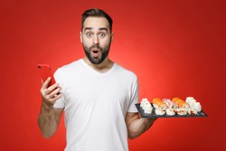 Shocked young man 20s in white t-shirt using mobile cell phone typing sms message hold makizushi sushi roll served on black plate traditional japanese food isolated on red background studio portrait