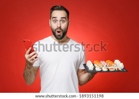 Shocked young man 20s in white t-shirt using mobile cell phone typing sms message hold makizushi sushi roll served on black plate traditional japanese food isolated on red background studio portrait Stok fotoğraf ©