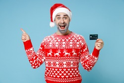 Shocked young Northern bearded man frozen snow face in Santa hat Christmas sweater hold credit bank card point finger up isolated on blue background. Happy New Year merry holiday winter time concept