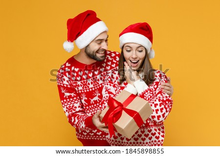 Shocked young Santa couple friends man woman 20s in red sweater Christmas hat hold present box with gift ribbon bow isolated on yellow background. Happy New Year celebration merry holiday concept