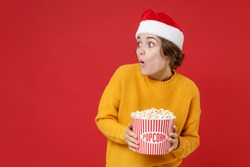 Shocked young Santa woman in casual yellow sweater Christmas hat hold bucket of popcorn looking aside isolated on red background studio portrait. Happy New Year celebration merry holiday concept
