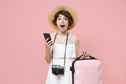 Shocked young tourist girl in summer dress hat with photo camera isolated on pink background. Traveling abroad to travel weekend getaway. Air flight journey concept. Using mobile phone, hold suitcase