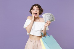 Shocked young woman girl in summer clothes isolated on violet wall background. Shopping discount sale concept. Hold package bag with purchases fan of cash money in dollar banknotes put hand on cheek