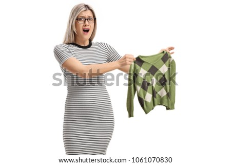 Shocked young woman holding a shrunken blouse and looking at the camera isolated on white background