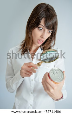Shocked young   woman inspecting a can?s nutrition label with a magnifying glass