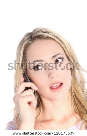 Shocked young woman with her mouth open listening to a call on her mobile phone isolated on white