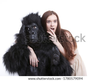 Shocked young woman with irritated man in gorilla costume against white background Photo stock ©