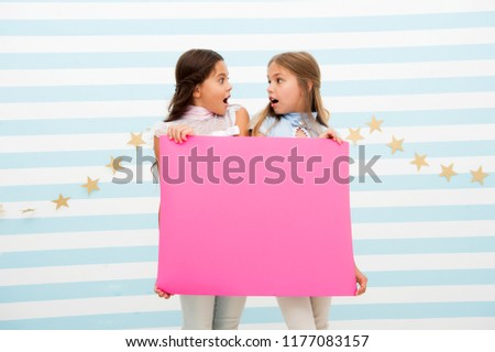 Shocking announcement concept. Amazing surprising news. Girl hold advertising banner. Girls kids holding paper banner for announcement. Shocked surprised children with blank paper copy space. #1177083157