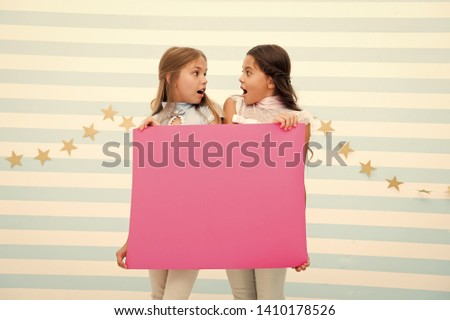 Shocking announcement concept. Amazing surprising news. Girl hold advertising banner. Girls kids holding paper banner for announcement. Shocked surprised children with blank paper copy space. #1410178526