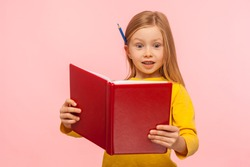 Shocking facts. Astonished smart little girl with pencil behind ear reading big book with surprised expression, amazed by story, learning encyclopedia. indoor studio shot isolated on pink background