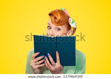 Shocking lines. Shocked amazed, surprised beautiful pinup retro hair style girl hiding herself behind a book with eyes wide open isolated yellow background copy space. Positive emotion face expression